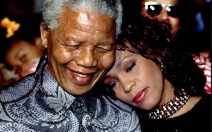Whitney Houston stands next to Mandela